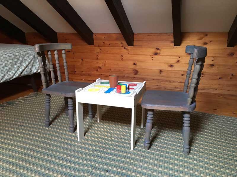 Parchis en mesita y sillas de niño en altillo
